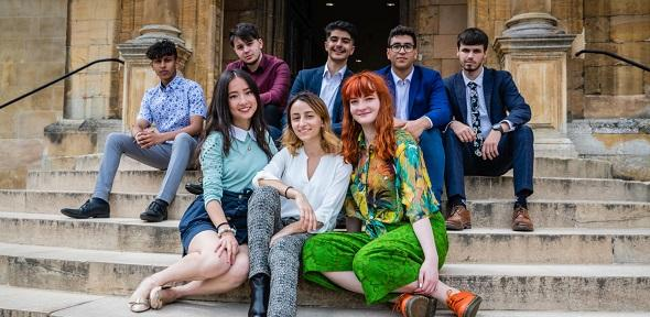 A group of Cambridge students seated on steps